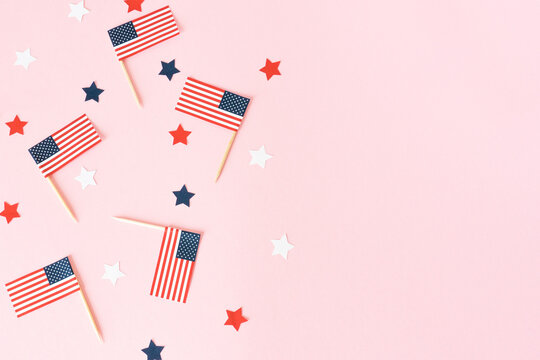 Many american flags and stars on pink background, flat lay. Celebration in America. 4th of july, happy usa independence day. Copy space for text.