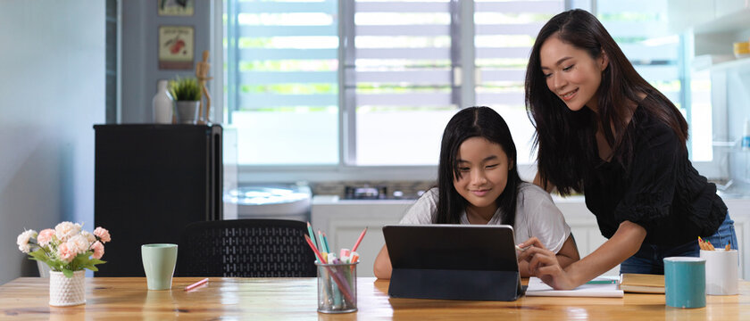 Mother helping her daughter do homework with digital tablet on wooden worktable in living room