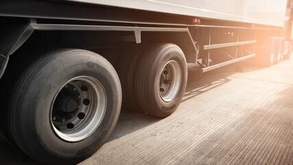 Closeup a truck wheels of semi truck trailer on parking. Road freight transportation.