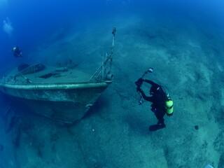 wreck dive underwater fish around ship wreck metal on ocean floor with scuba divers