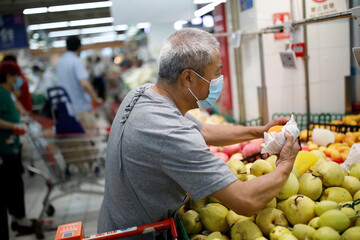 Man shops at the fruit section inside a supermarket in Beijing