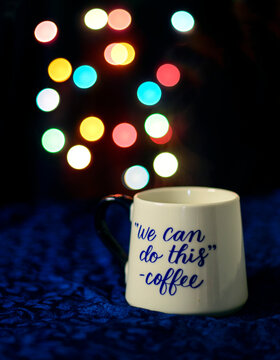 """""""We can do this quote by coffee"""" - white cup on a blue velvet cloth and bokeh lights in the background"""