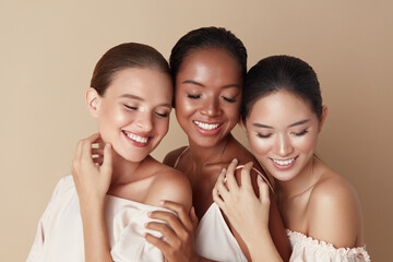 Beauty. Diverse Group Of Ethnic Women Portrait. Happy Different Ethnicity Models Standing Together With Closed Eyes And Smiling. Gorgeous Multi-Ethnic Girls With Nude Makeup Against Beige Background.