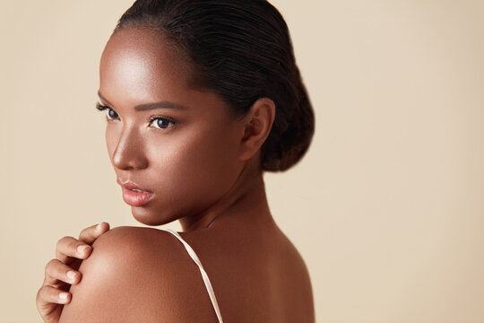 Beauty. Mixed Race Woman Portrait. Beautiful Ethnic Model Touches Her Shoulder And Looking Away. Female With Perfect Glowing Skin And Nude Natural Makeup Posing Against Beige Background.