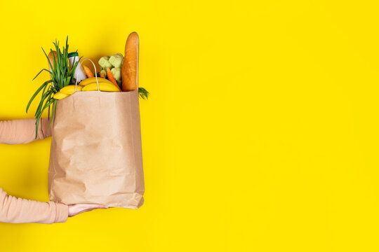 Girl or woman holds a paper bag filled with groceries such as fruits, vegetables, milk, yogurt, eggs isolated on yellow.