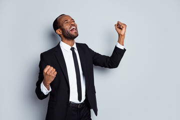Portrait of delighted afro american man banker economist get new job raise fists scream yes wear...