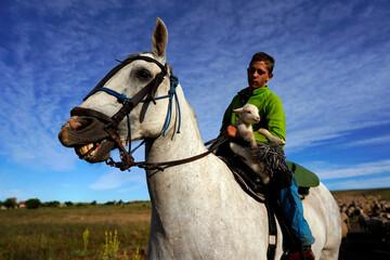 Manuel Moran holds a newborn lamb as he rides a horse amid the coronavirus disease (COVID-19) outbreak in Villalobar