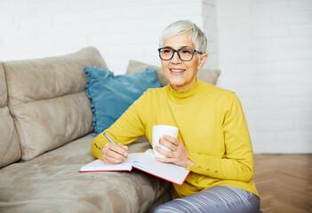 beautiful senior mature woman portrait gray hair writing notebook pen note work book cup coffee tea...