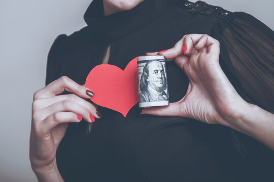 I love money! Business woman holding heart and cash as symbol of love for US Dollars.