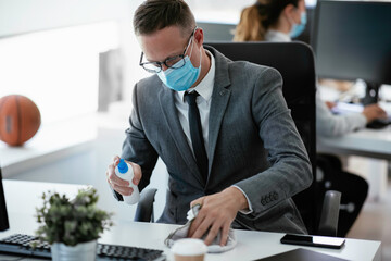 Handsome businessman disinfecting desk in the office.
