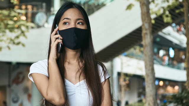 Woman wearing a mask and using a smartphone for business, social media, working and waiting for someone in the public.
