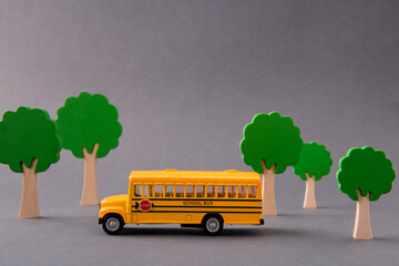 Art design picture of school bus taking kids from home to primary school among tress isolated over gray pastel color background