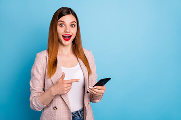 Portrait of shocked positive cheerful girl use smartphone impressed incredible social network sales promo point index finger screen wear plaid jacket isolated over blue color background