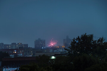 Illegal fireworks illuminate the sky over the skyline of the Brooklyn borough of New York City, New York