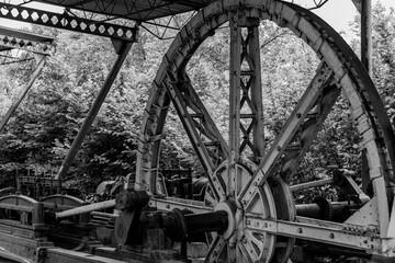 Obraz Widok na koło zamachowe starej maszyny parowej w czerni i bieli - fototapety do salonu