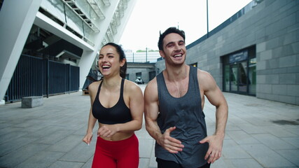 Close up cheerful couple running outdoor. Laughing man and woman training run