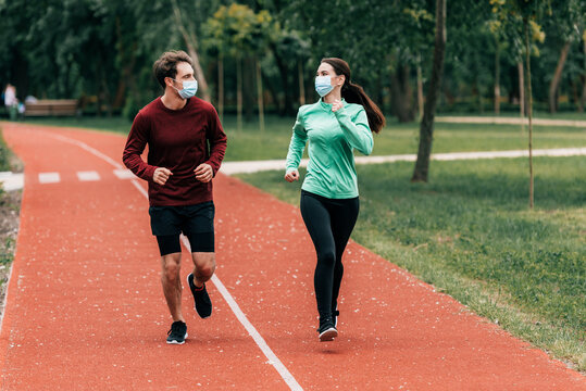 Runners in medical masks looking at each other while training on running track in park