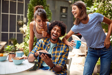 Young guy showing funny content of mobile to his friends
