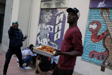African immigrant Modu carries a meal tray donated by Monaco soccer player Keita Balde, for distribution to compatriots living on the streets while waiting for available fruit picking jobs, in Lleida