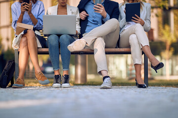 businesspeople sitting on bench outdoor with focus on legs, checking their cell phones, laptop, tablet. body language concept
