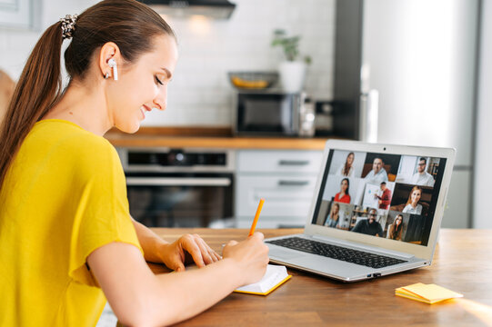 Side view of young woman watching on laptop display with a group of multiracial people on it and writing notes. Video call, online conference, webinar