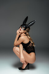 Side view of sexy woman in bodysuit, heels and rabbit mask touching lips on grey background