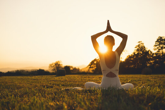 Young woman practicing yoga on nature.