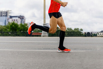 Fotomurales - man runner in black compression socks run city marathon