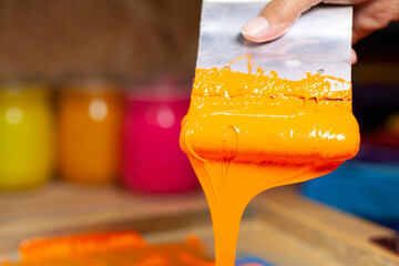 .orange color dripping from hand screen printing during printing tee shirt .in tee shirt factory.