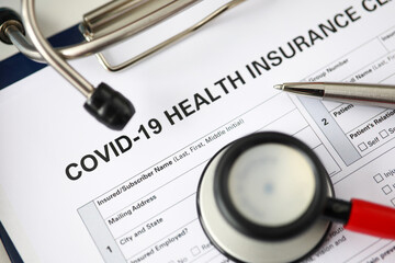 Silver pen lying at covid-19 insurance claim blank