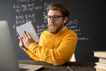 Confident teacher in eyeglasses and pullover pointing at his notes in copybook