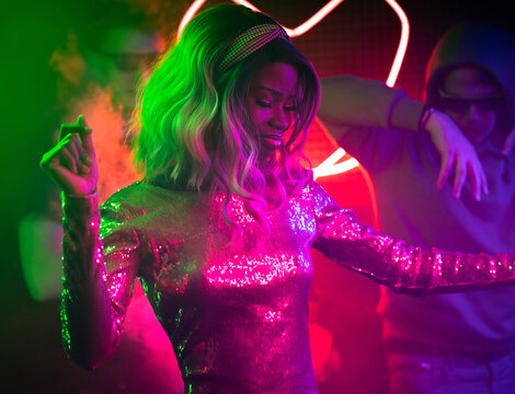 Young African American woman dancing in disco club among her fans. Sexy women wearing shiny dress have fun dancing with friends. Nightlife concept.