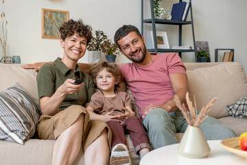 Young woman with remote control, her husband and their little son watching tv