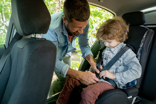Young man helping his cute little son to put seatbelt while going to countryside