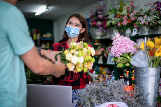 Asian Woman wearing  face mask or protective mask against coronavirus crisis, Florist owner of a small florist business holding flowers for delivery to customers at her store
