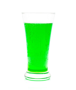 Green sparkling water in a glass on a white background