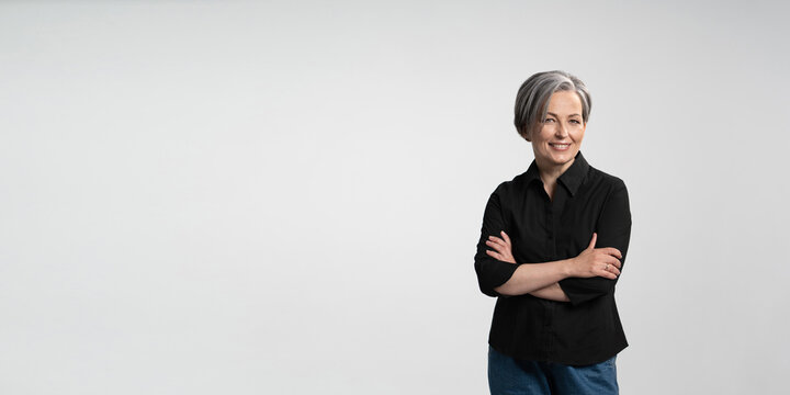 Confident mature woman smiling arms crossed. Gray haired businesswoman in black shirt on white background. Horizontal template for ad banner with copy spase for text.