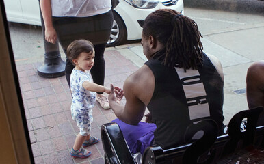 A child shakes hands with a man in front of Black Wall Street t-shirt store in Tulsa, Oklahoma