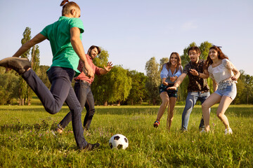 Young friends playing football game on green meadow. Students having fun on summer weekend in nature