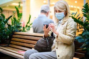 Masked woman using her cellphone while sitting in a shopping centre