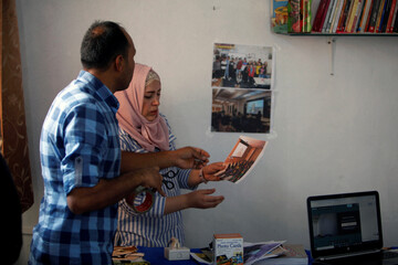 Syrian refugee couple, Shadi Abdullah Khalid and his wife Hadia Ahmad who has recovered from cancer, look at the pictures of their Arabic online classes at home, following the outbreak of the coronavirus disease (COVID-19), in Qushtapa camp, in Erbil
