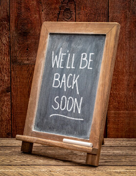We will be back soon - white chalk handwriting on a blackboard, business reopening after coronavirus pandemic.