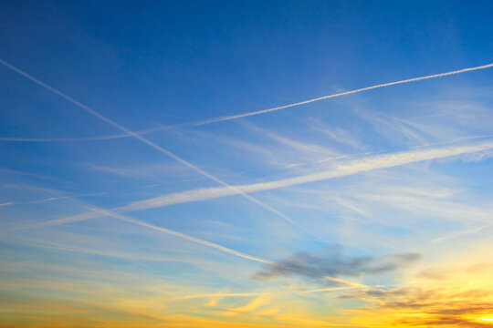 Beautiful evening cloudscape - Intercrossing airplane contrail against the background of bright blue sky with diffused white clouds in the light of rising sun