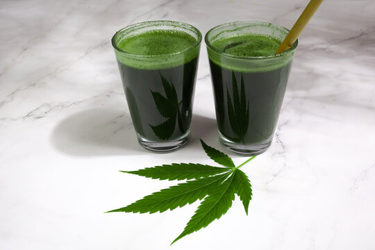 Healthy green cannabis smoothie on marble background
