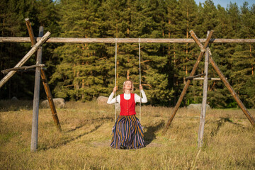 Latvian woman in traditional clothing on a swing.