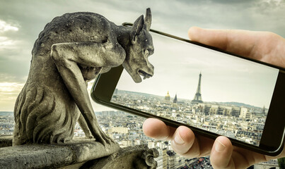 Gargoyle on Cathedral of Notre Dame de Paris looks at Eiffel Tower in mobile or cell phone, Paris, France. Funny photo of old Paris and smartphone.