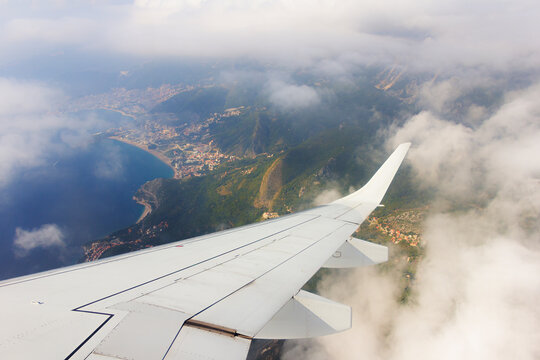 Wing of airplane flying above the clouds and coast and mountains of Montenegro, Europe