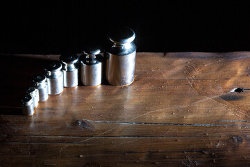 set of small weights for jewelry scales on a wooden table. front and background blurred with bokeh effect