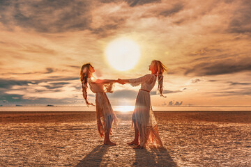 two beautiful girls having fun at sunset on the beach