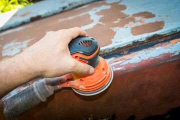 Man's hand operates a disc/orbital sander, to remove paint and rust from metal doors Wall mural